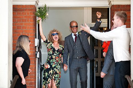 A bright summer wedding with a couple leaving Mayfair Library with arms aloft and sunglasses in place