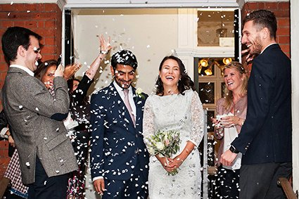 An Italian bride and groom leave their Autumn register office wedding in the rain so guests threw confetti in the porch at Mayfair Library