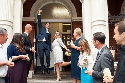 A groom jumps for joy after his civil wedding ceremony at Mayfair Library (Westminster Register Office)
