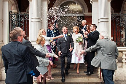 A bride and groom leaving Mayfair Library under confetti after their Marylebone Room ceremony