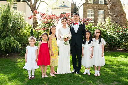 A bride and groom and the flowergirls pose for a group portrait in Mount Street Gardens next door to Westminster's Mayfair Library wedding venue