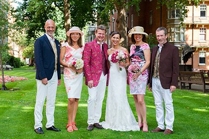 A group photograph in Mount Street Gardens for this French couple and their friends after their Mayfair Library wedding ceremony