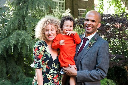 A couple and their young daughter pose for a photo after their Mayfair Library wedding ceremony