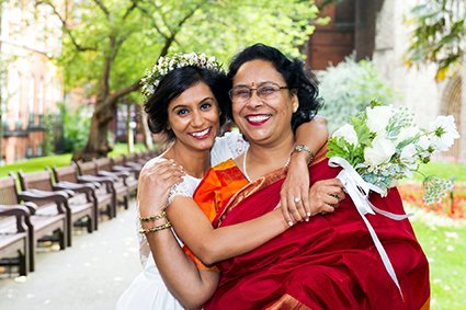 An Indian bride hugs her mother in Mount Street Gardens after her civil wedding ceremony in the Mayfair Room at Westminster Register Office