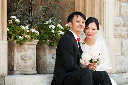 A bride and groom sat on a sandstone step after their Old Marylebone Town Hall wedding