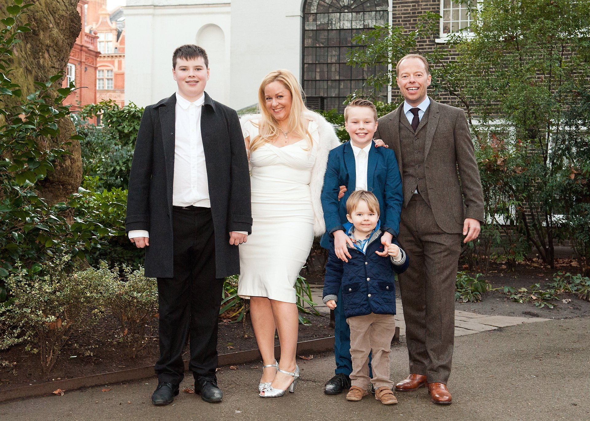 A family in Mount Street Gardens at dusk just before a wedding at next door Mayfair Library and the Marylebone Room