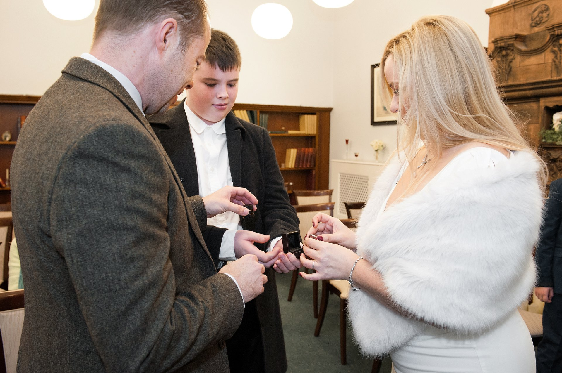 Son brings the rings for his father during a Christmas wedding at Mayfair Library