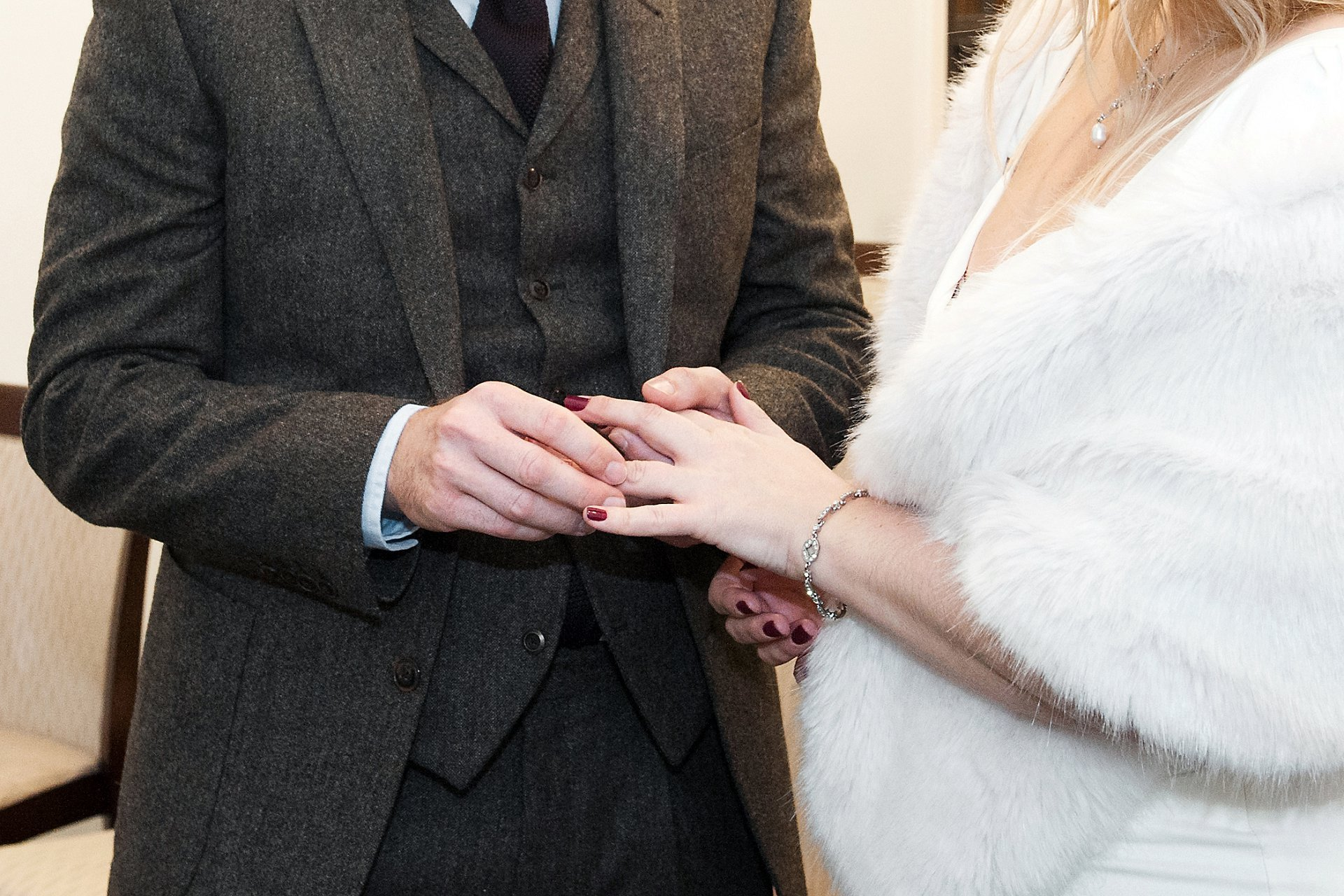 The groom places the wedding band on his bride's finger during this Marylebone Room ceremony at Mayfair Library