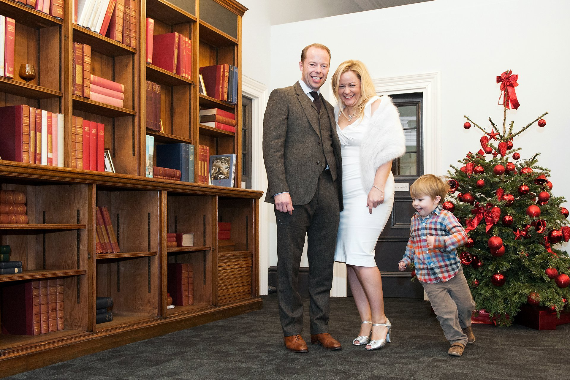 Westminster Register Office Christmas wedding showing a bride and groom and their small son running around them in the Mayfair Room at Mayfair Library next to a decorated Christmas tree (photo Emma Duggan Photography)
