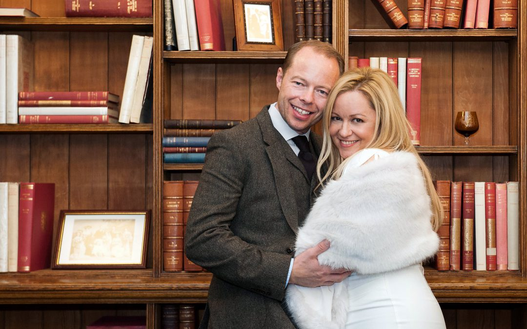 Westminster Register Office Christmas wedding at Mayfair Library with this bride and groom posing in front of the bookcase because it is dark outside for their December wedding