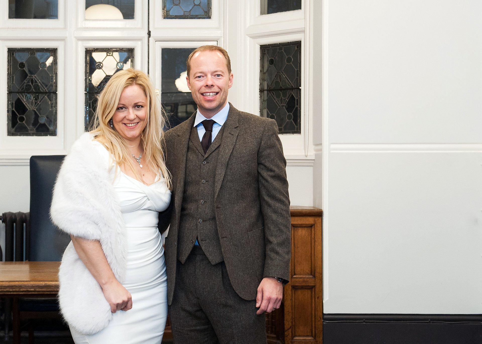 A bride and groom in the Mayfair Room at Westminster Register Office after their Christmas wedding in December, the photogrpah showing that it is dark outside