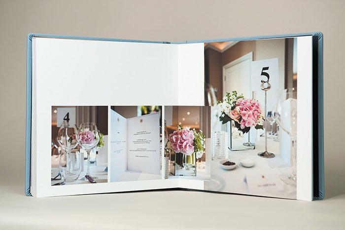 Wedding album from a Chelsea Register Office wedding showing pink flower table details in a blue leather-bound album. Photo: Chelsea Register Office wedding photographer Emma Duggan
