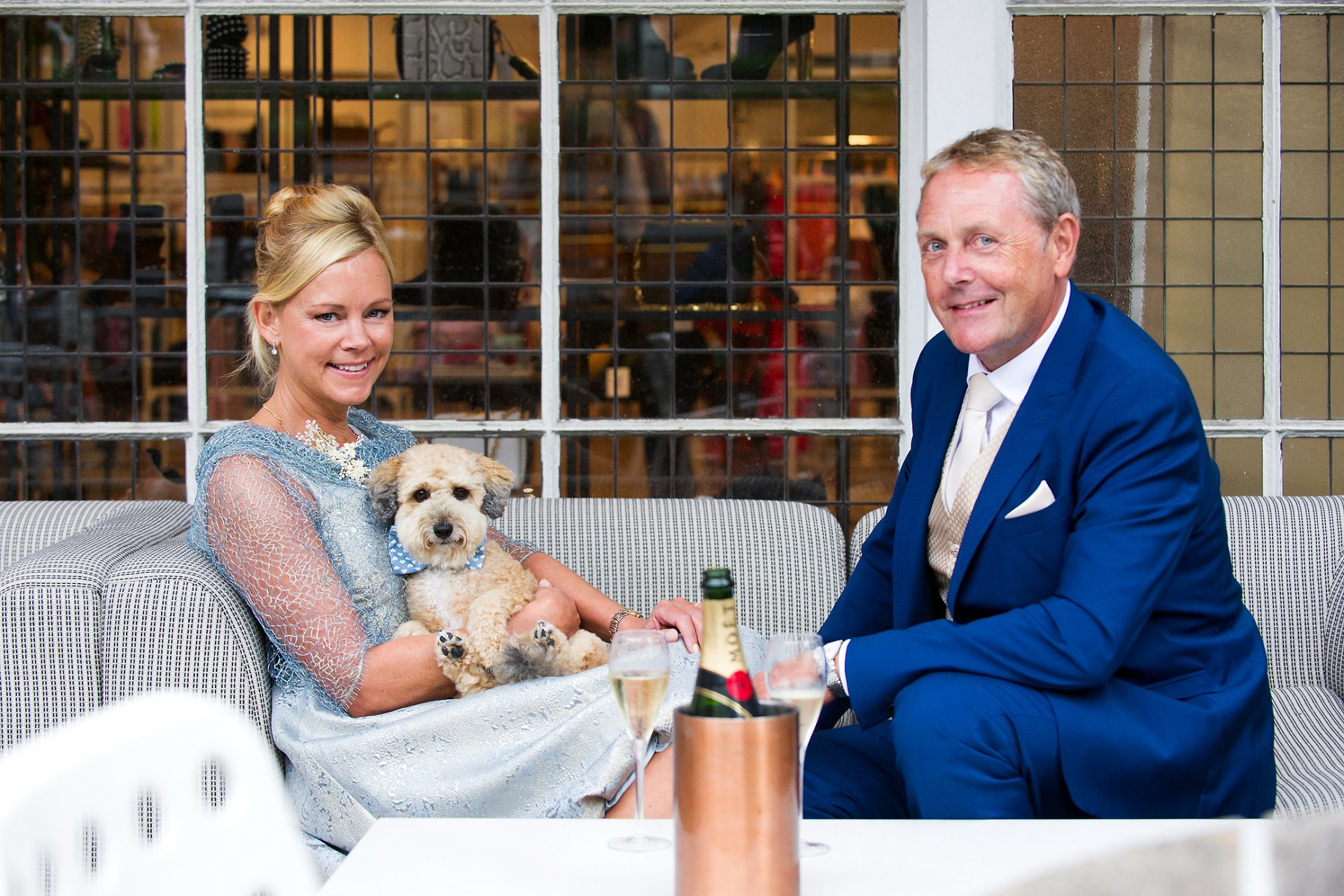 bluebird chelsea drinks reception - a couple and their little dog celebrate their wedding with chapagne at bluebird restaurant