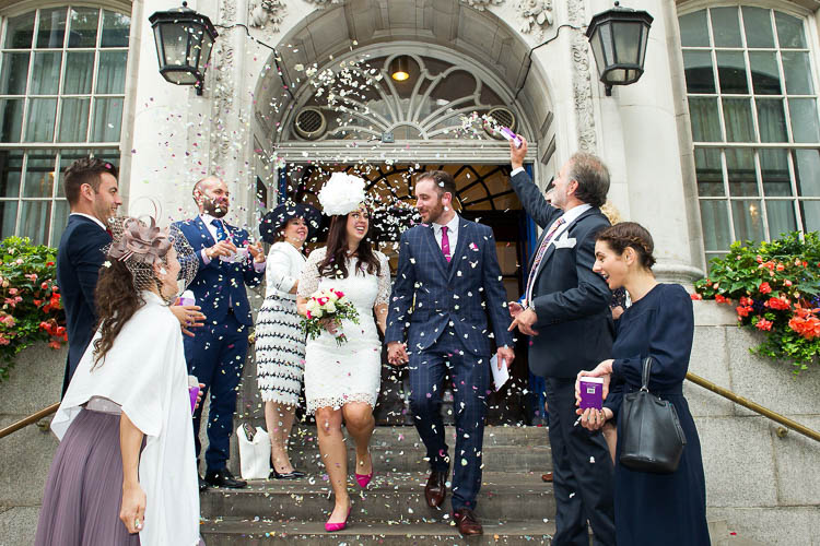 A bride and groom step out onto the Kings Road steps of Chelsea Registry Office in a whirl of confetti after their civil marriage ceremony. PHOTO: Chelsea Register Office wedding photographer Emma Duggan.