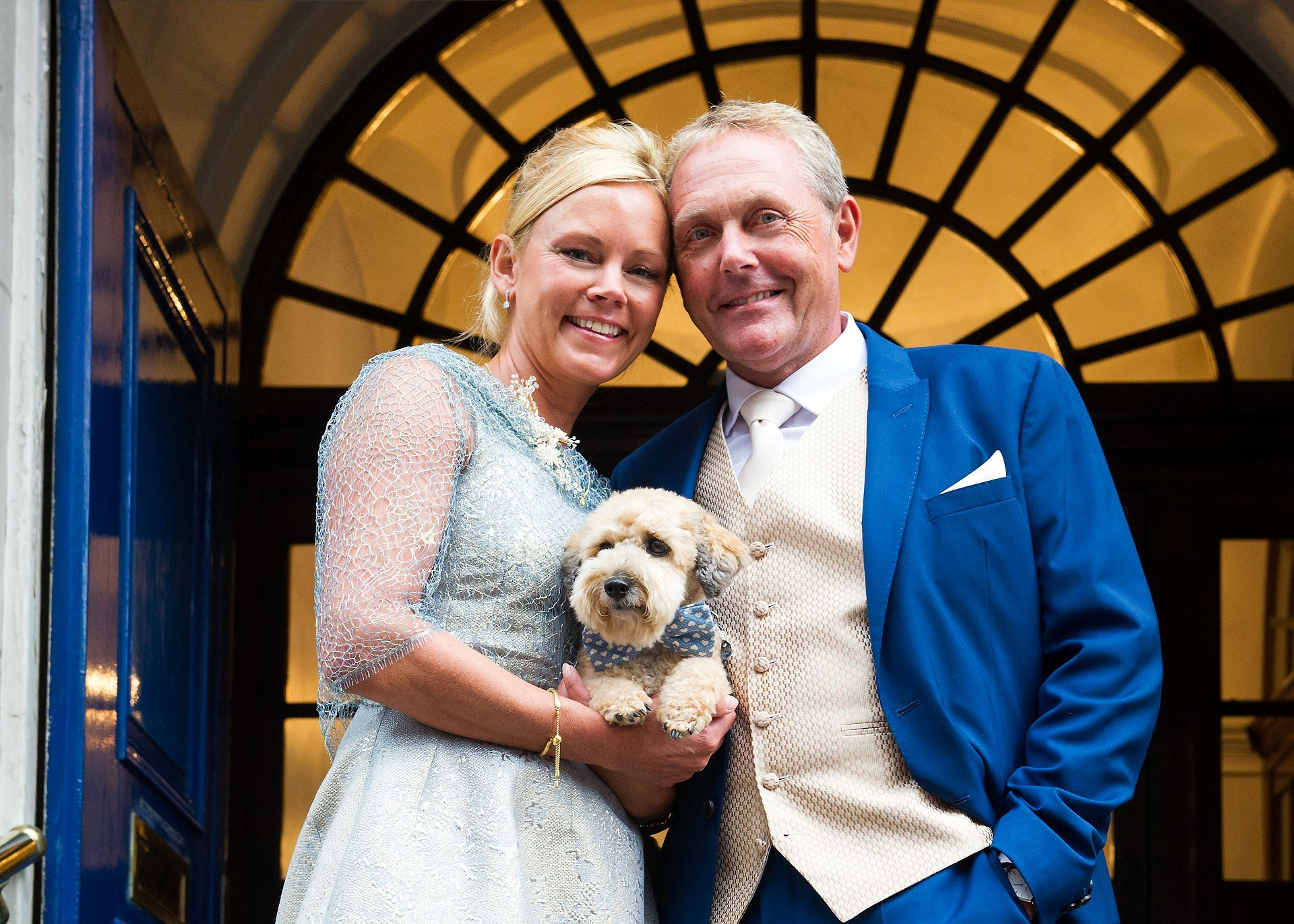 bring your dog to your chelsea wedding - a bride and groom on the steps of chelsea register office holding their jackapoo, jimmy