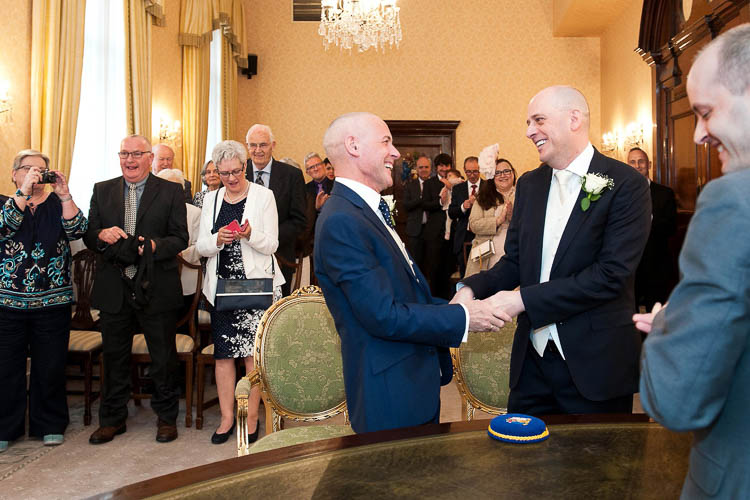 Two grooms exchange vows in the Brydon Room at Chelsea Old Town Hall. Photo: Chelsea Register Office wedding photographer Emma Duggan