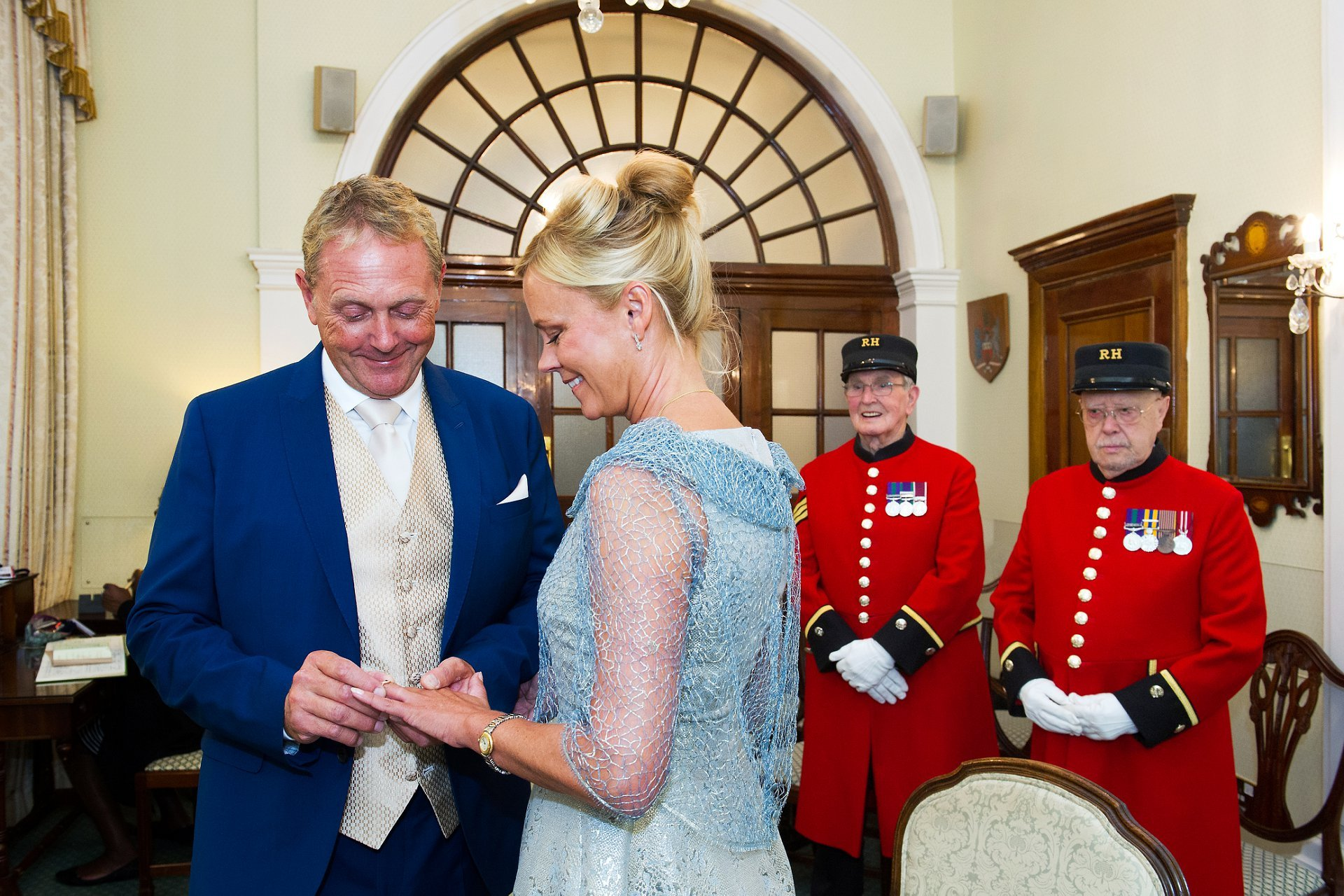 chelsea old town hall wedding photography showing a groom placing a ring on his bride's finger watched by two chelsea pensioners in the rossetti room