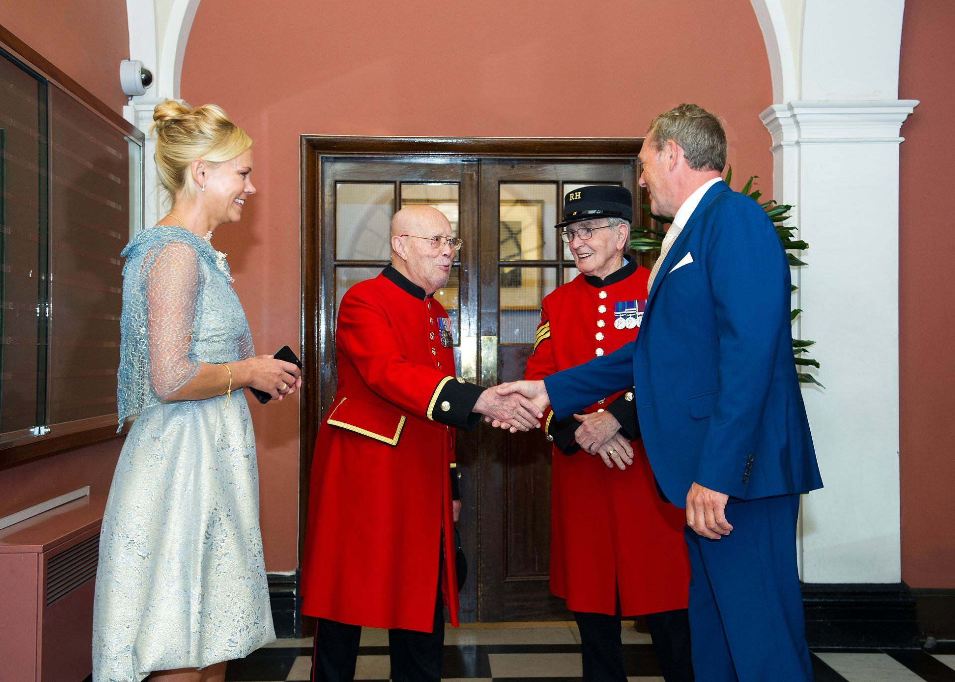 A groom shakes hands with a chelsea pensioner in the waiting area at chelsea old town hall