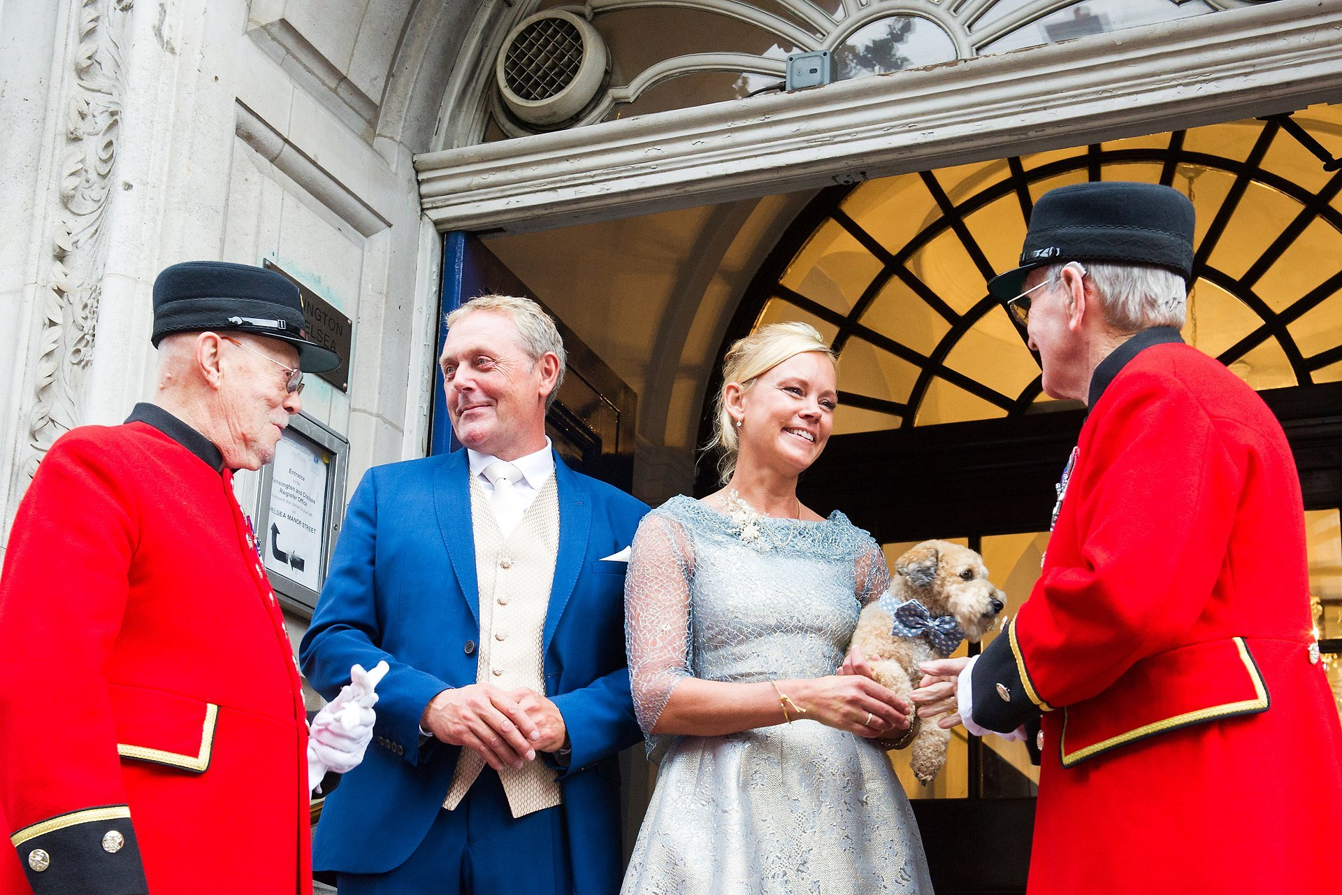 chelsea registry office wedding photography with a bride and groom and two chelsea pensioners on the steps after their civil wedding ceremony