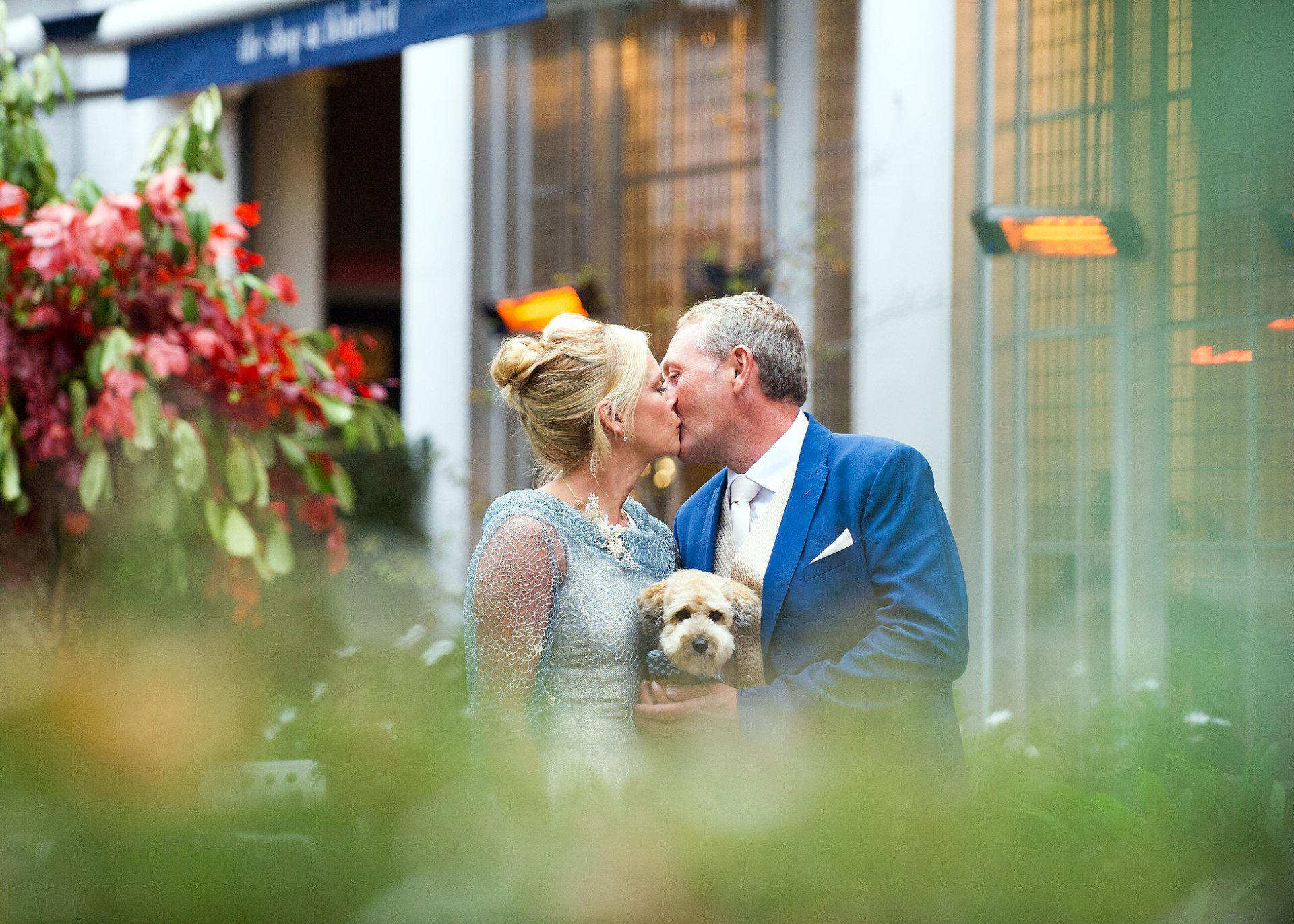 dog wedding photographer london showing a bride and groom with their little jackapoo just before their civil marriage ceremony at chelsea register office