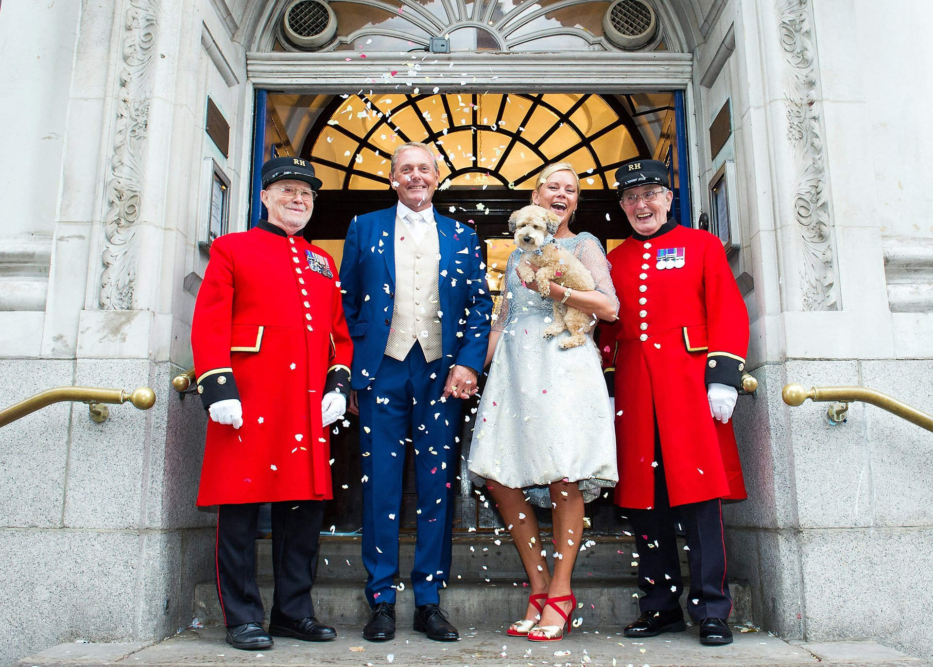 dog wedding photography london showing a bride and groom holding their little dog - a jackapoo - on the steps of chelsea register office with confetti thrown by their chelsea pensioner witnesses