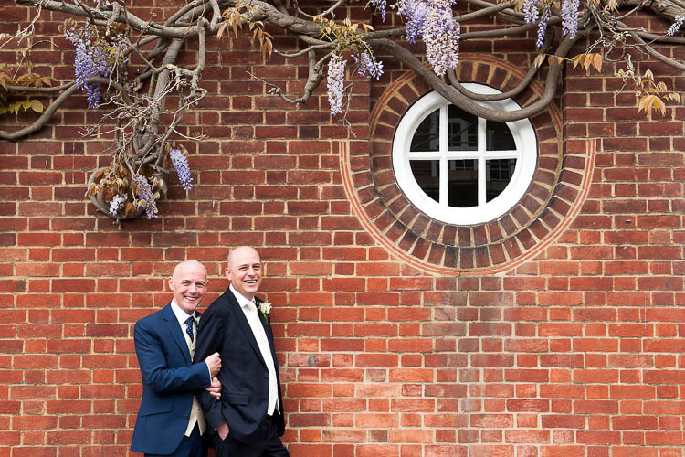 Two grooms pose for wedding portraits against the architecture of London's Royal Borough of Kensington and Chelsea.