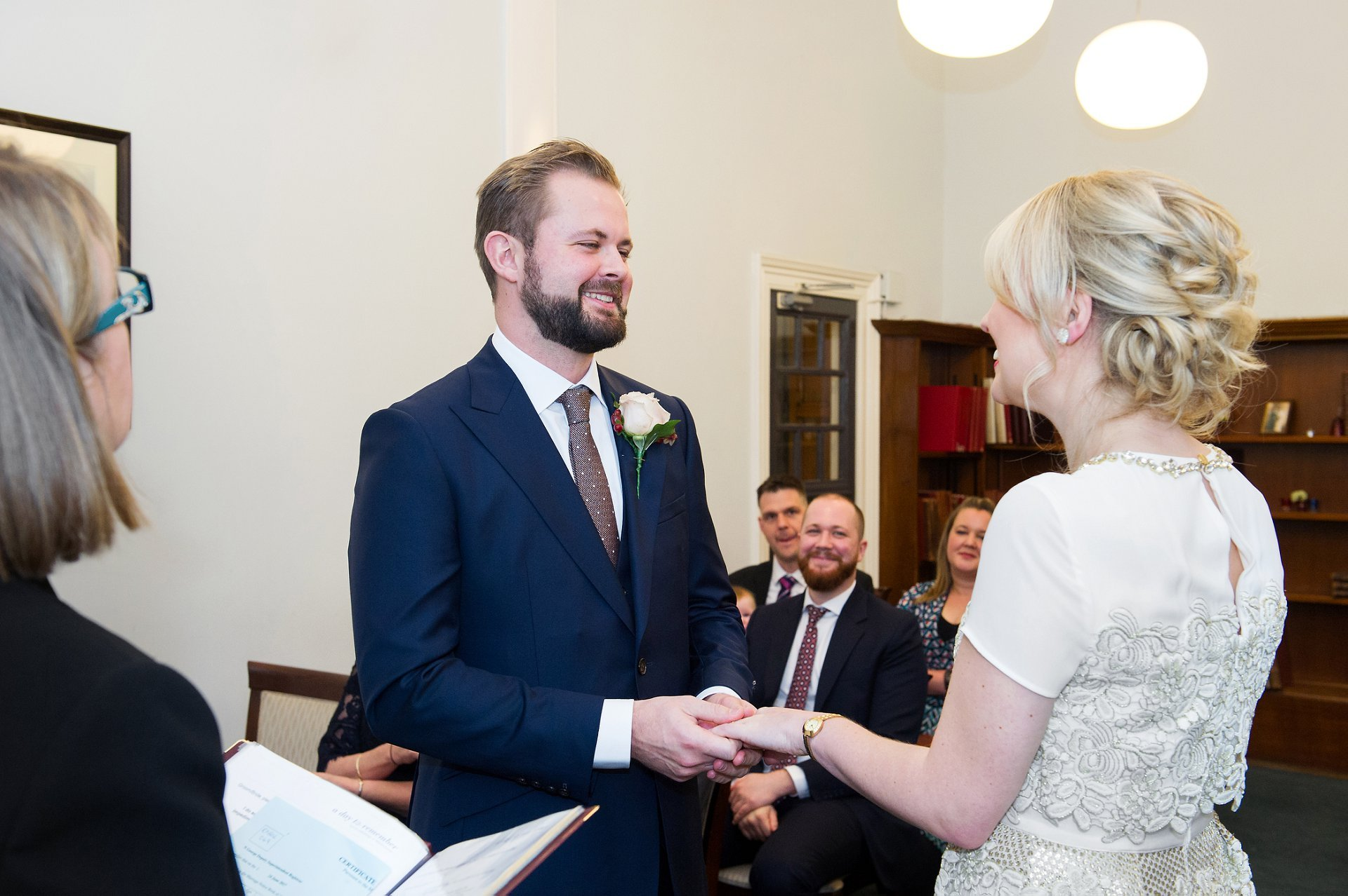 a bride and groom during the exchange of rings at westminster registry office