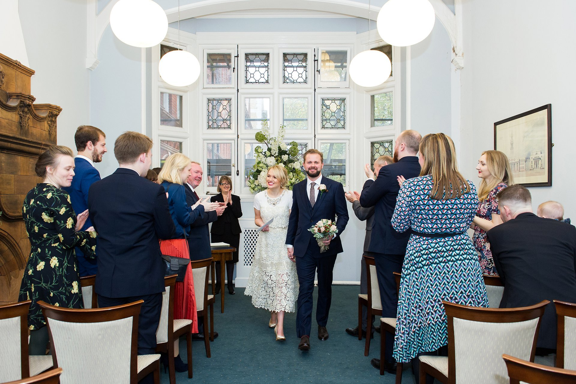 a bride and groom leaving the marylebone room after their london marriage ceremony