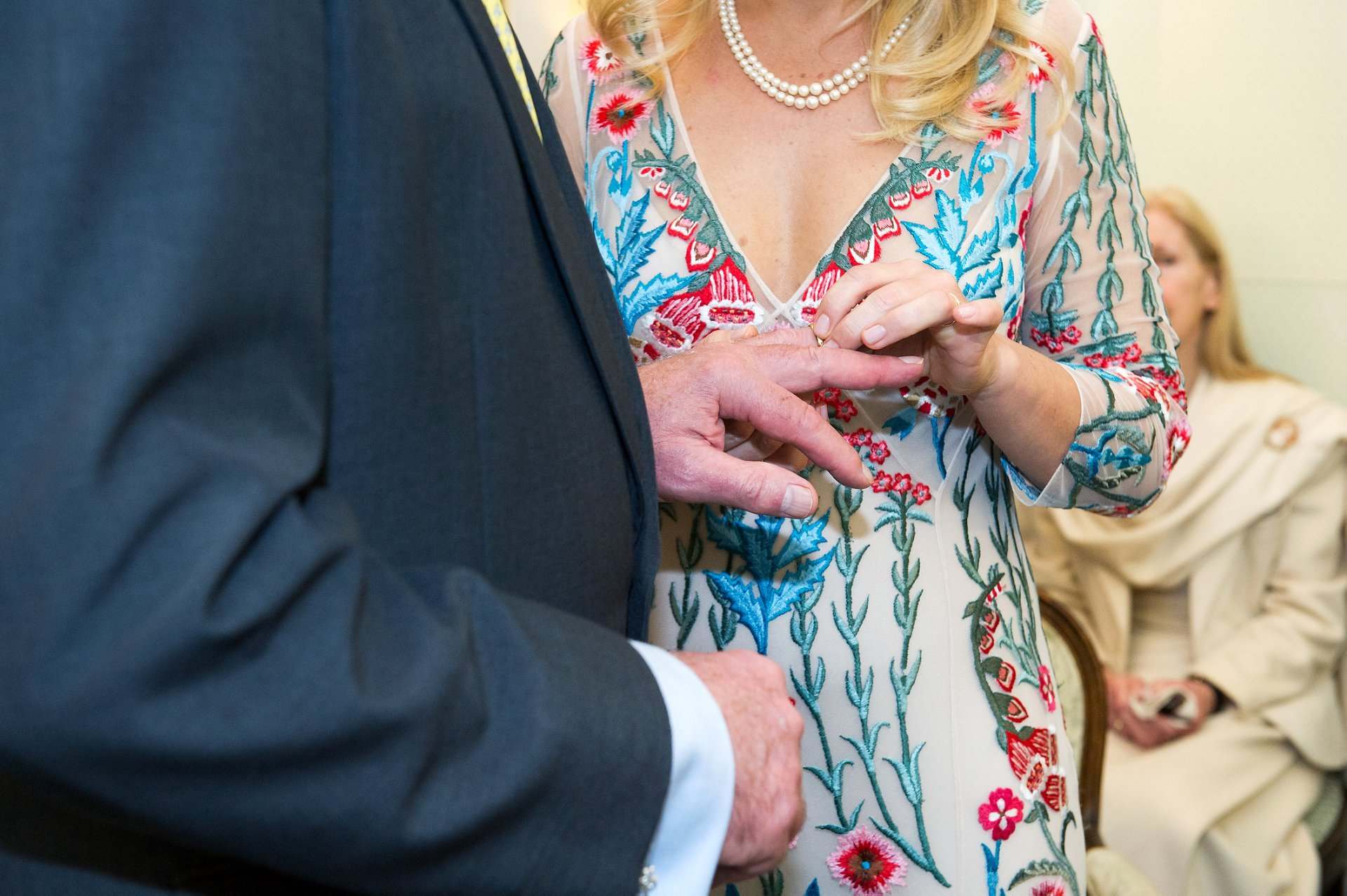 a bride puts wedding band on husband's finger during this chelsea old town hall wedding