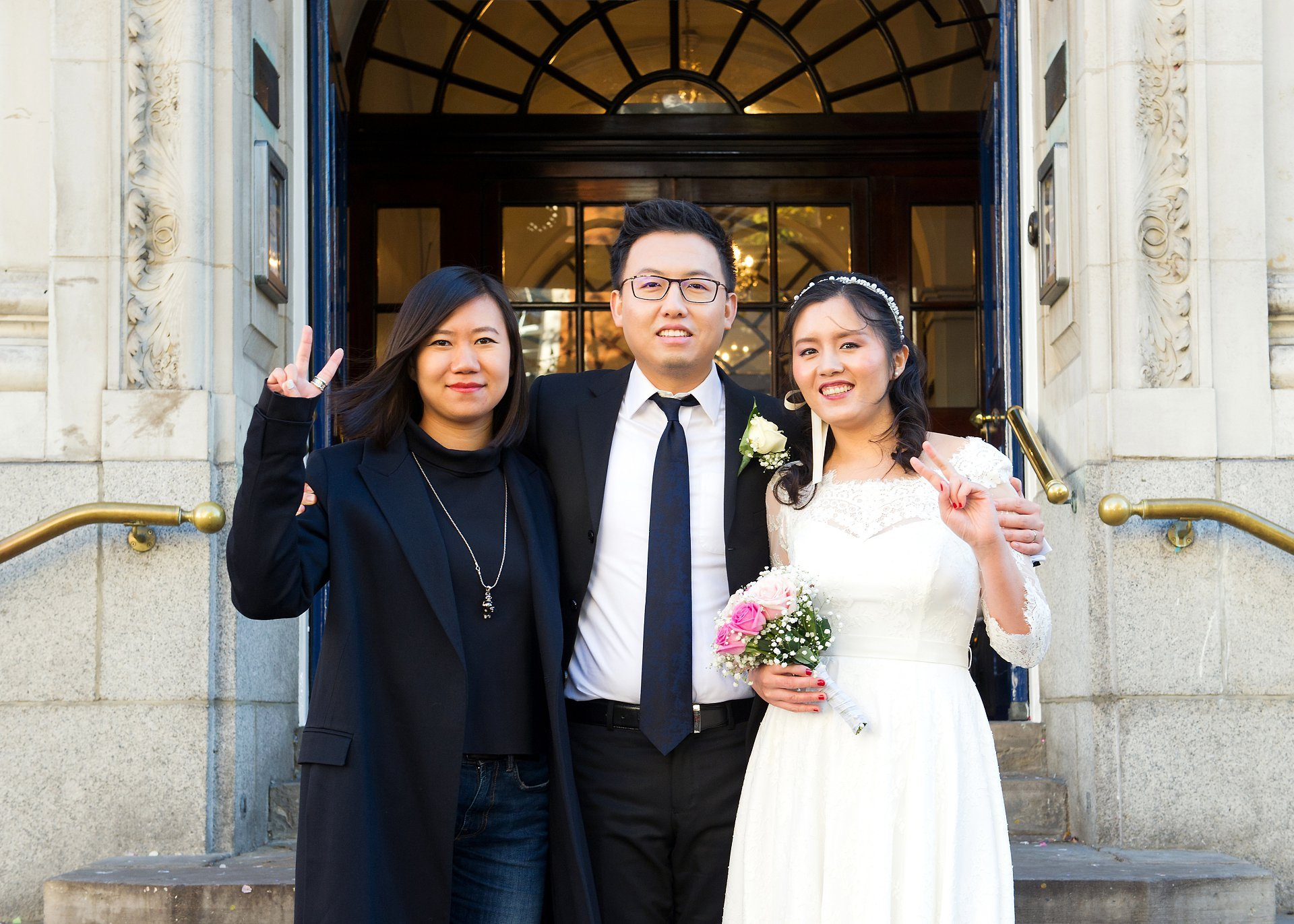 a chinese couple and one of their wedding guests on the steps of chelsea old town hall