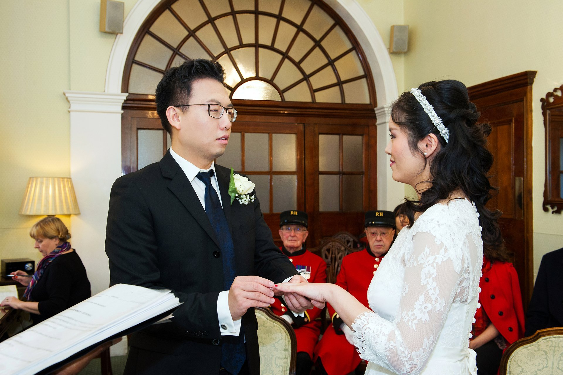 a chinese groom places the ring on his chinese bride's finger in the rossetti room
