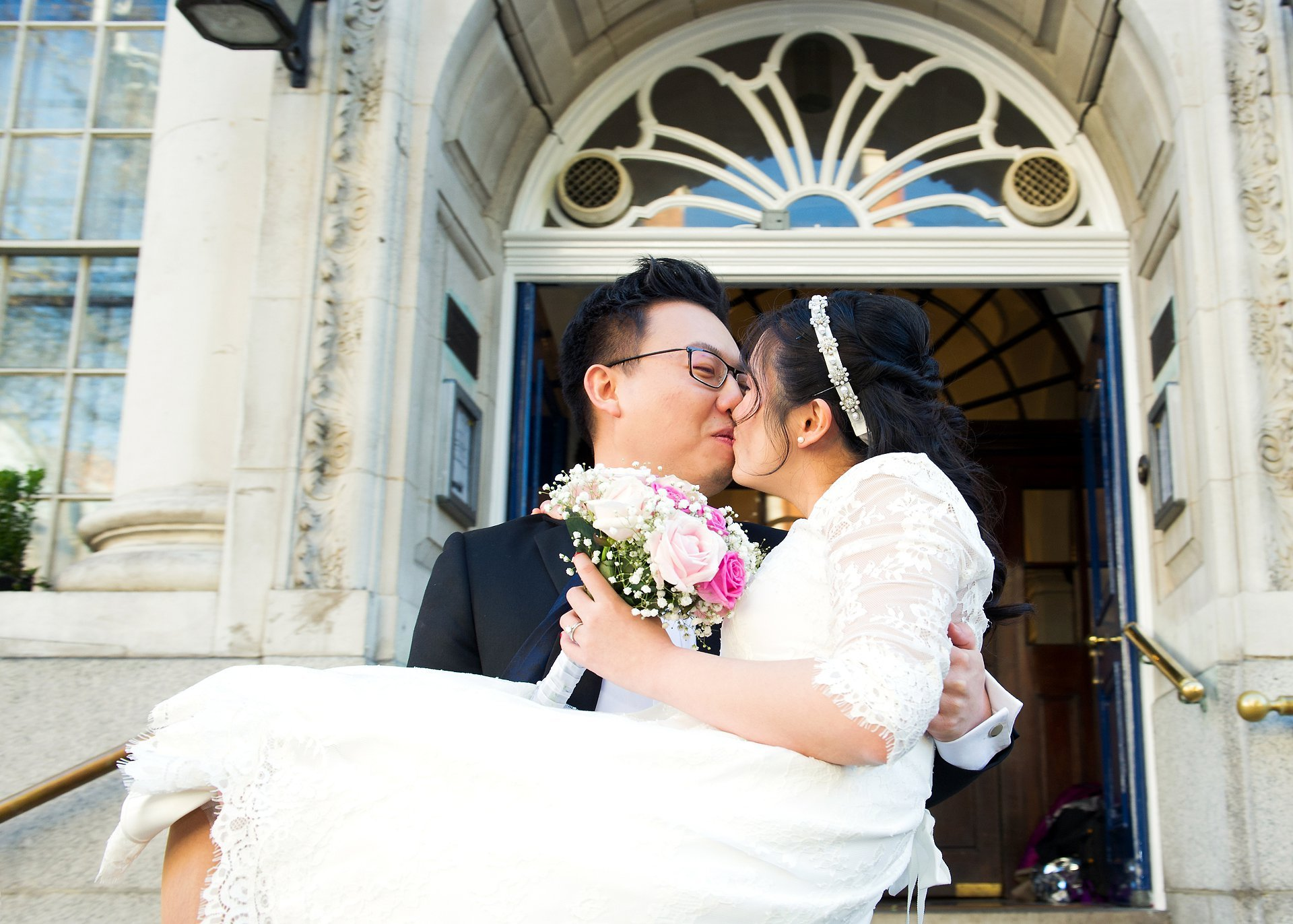 a couple celebrate their chinese wedding chelsea old town hall with a kiss on the king's road steps