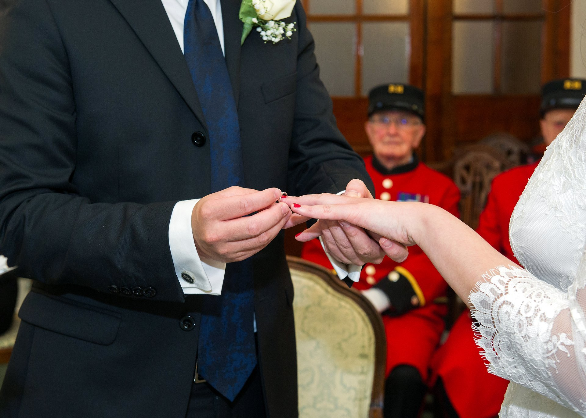 a couple exchange rings at chelsea registry office watched by two chelsea pensioners