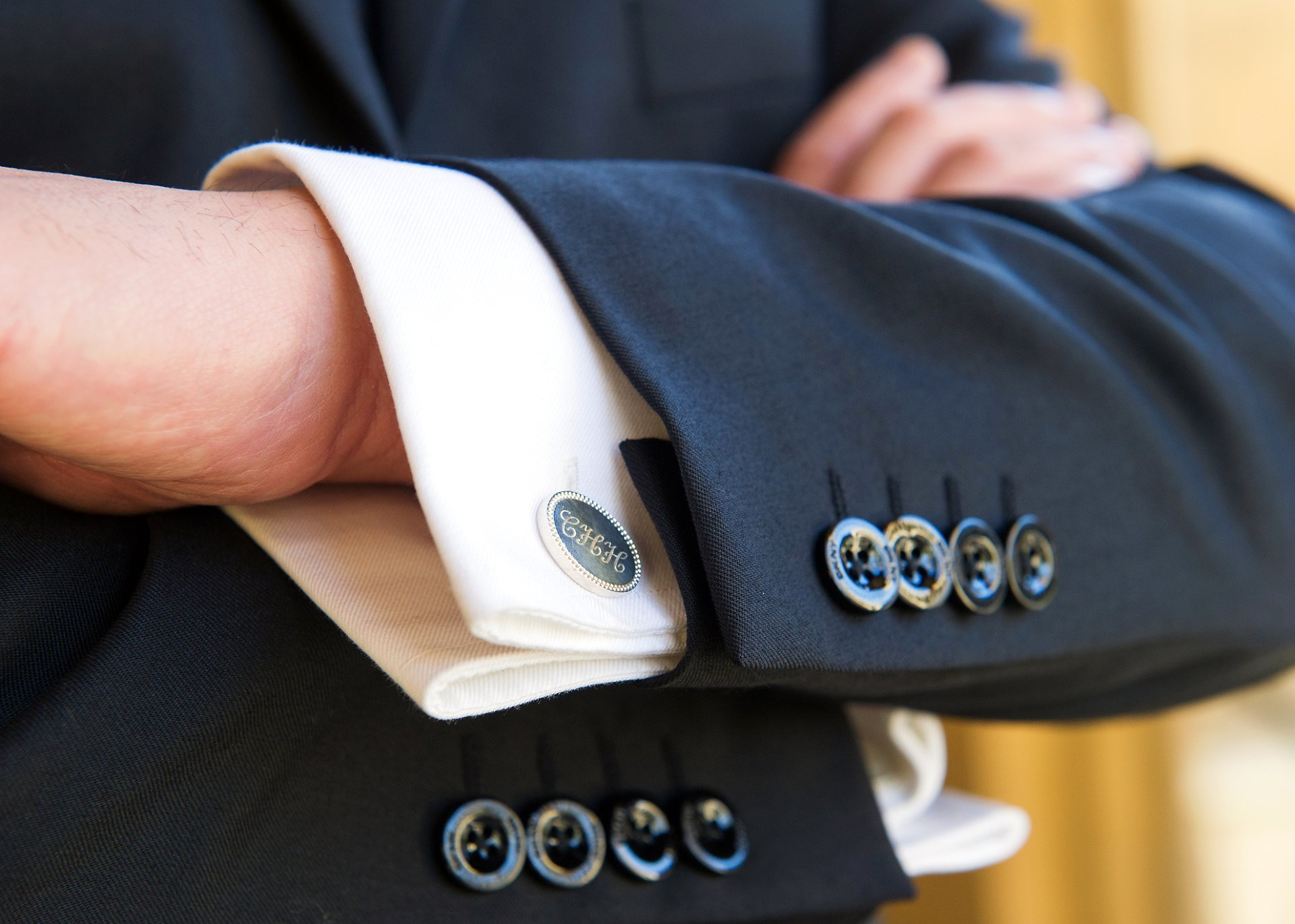 a groom crosses his arms to show cufflinks with his initials on his wedding day in london