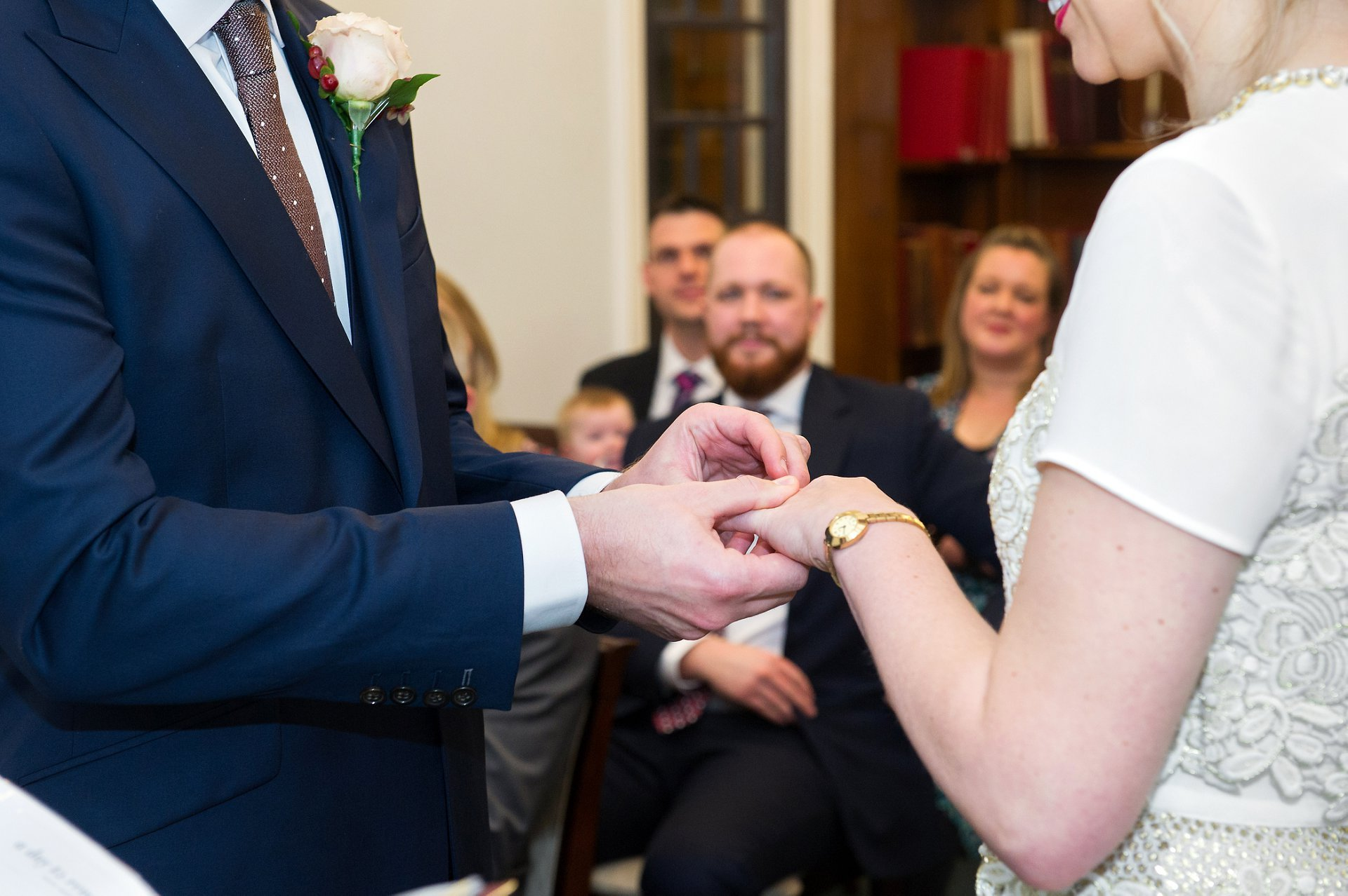 a groom places the ring on his bride's finger during this mayfair wedding
