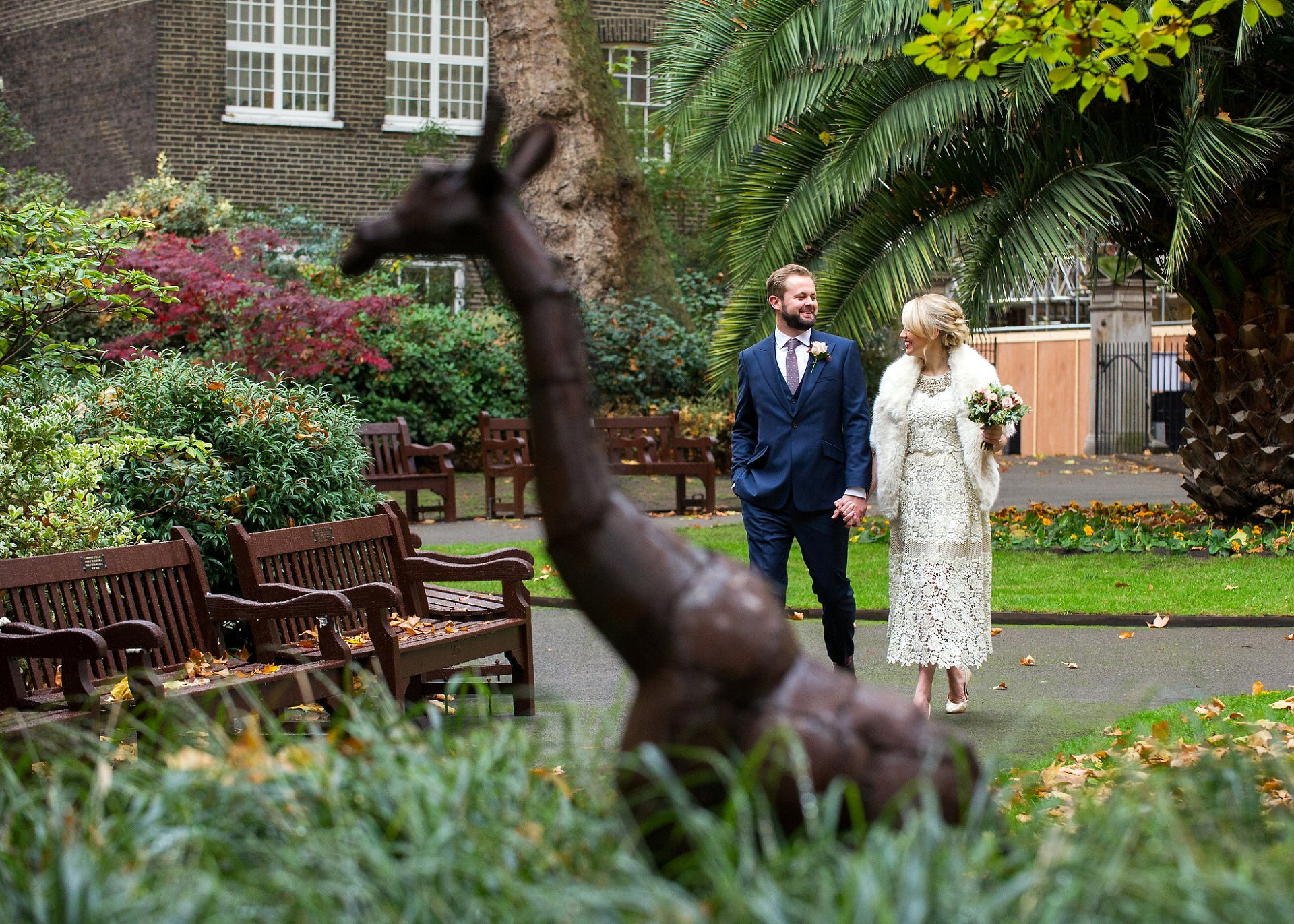 bride and groom walk through mount street gardens with the metal giraffe in the foreground