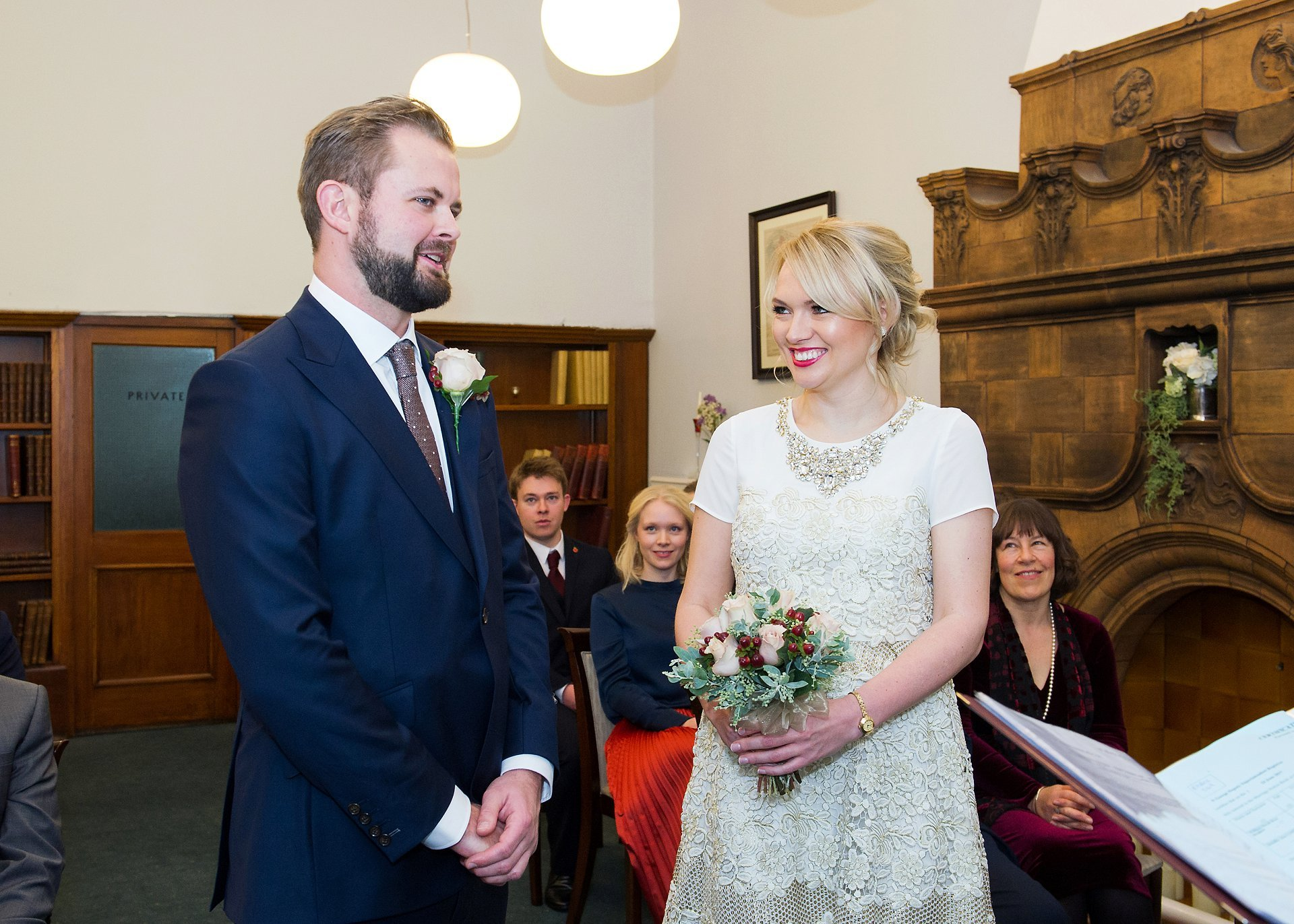bride smiles as groom says his vows during this mayfair library ceremony