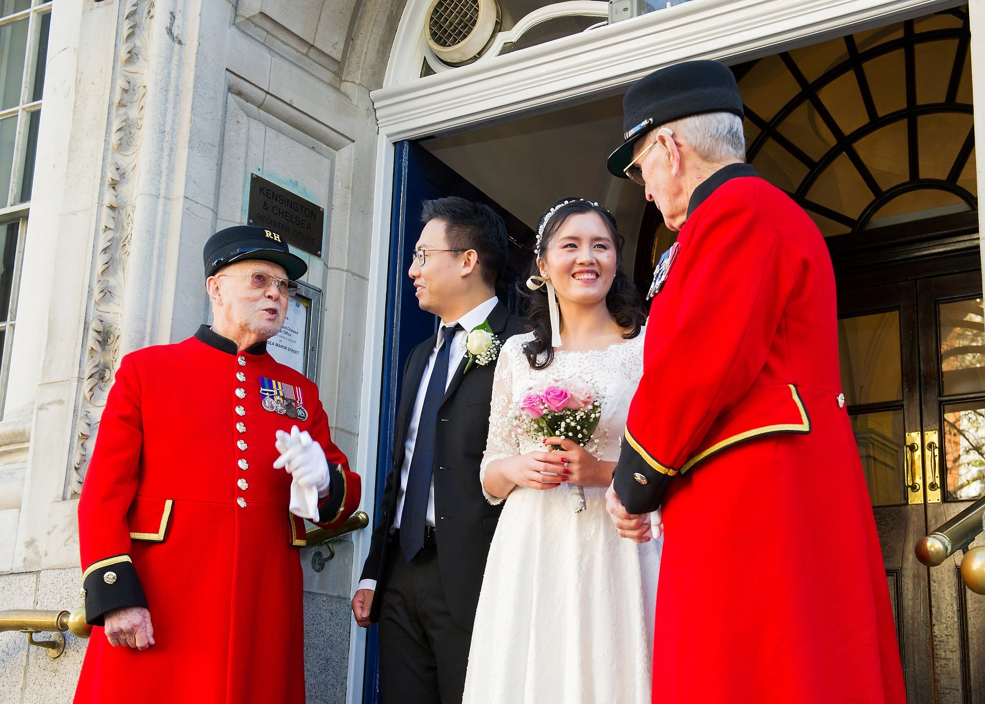 chelsea pensioners and a bride and groom outside chelsea register office