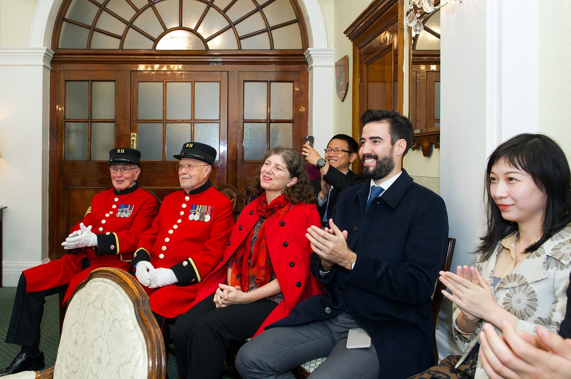chelsea pensioners from the royal hospital and guests clap the bride and groom at chelsea