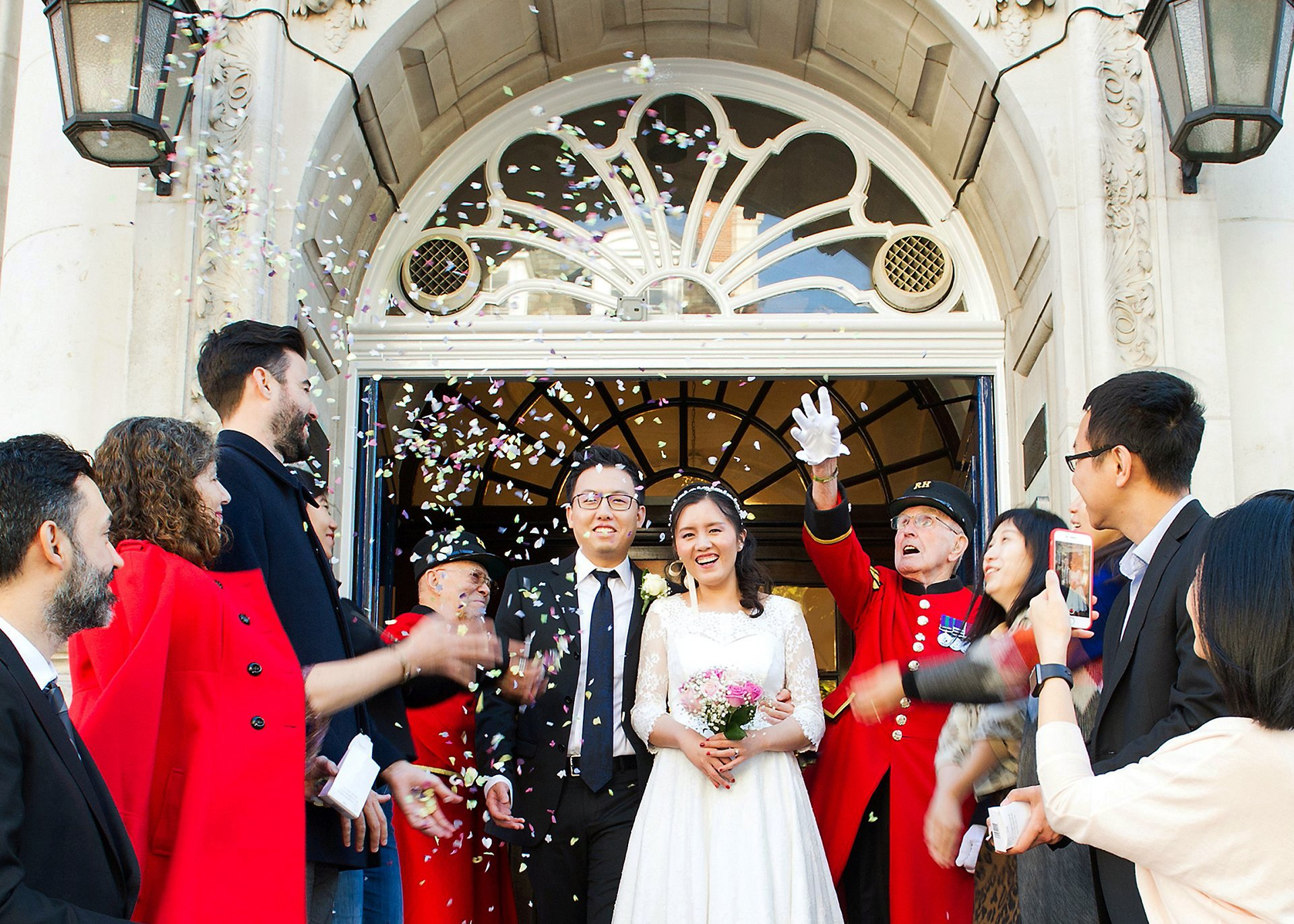 chinese wedding chelsea old town hall with the bride and groom on the famous steps with confetti