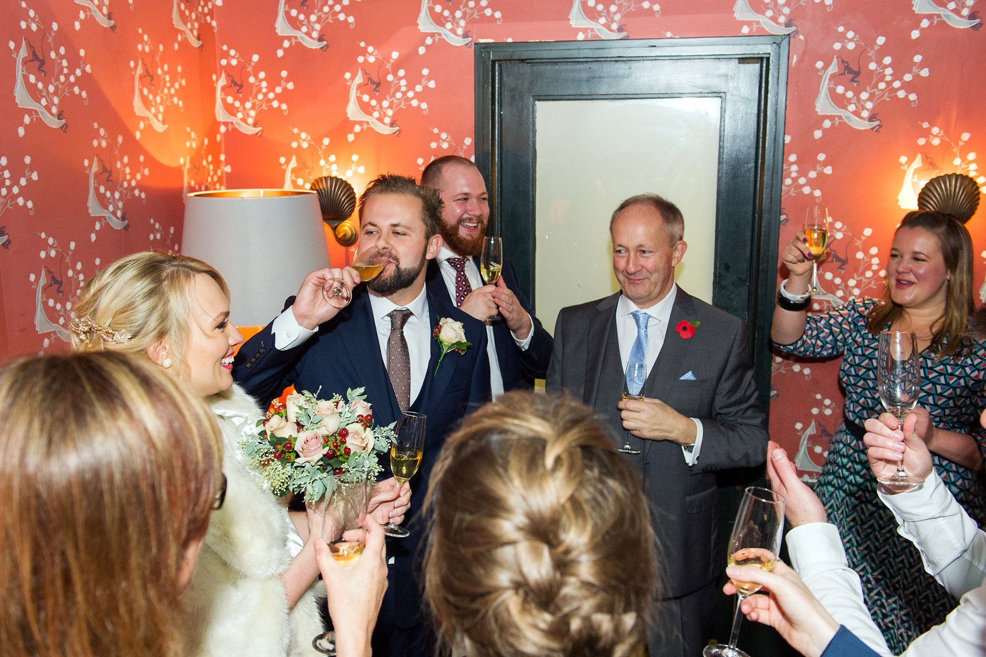 the groom and guests toast the bride at bocca di lupo in soho just before their wedding meal
