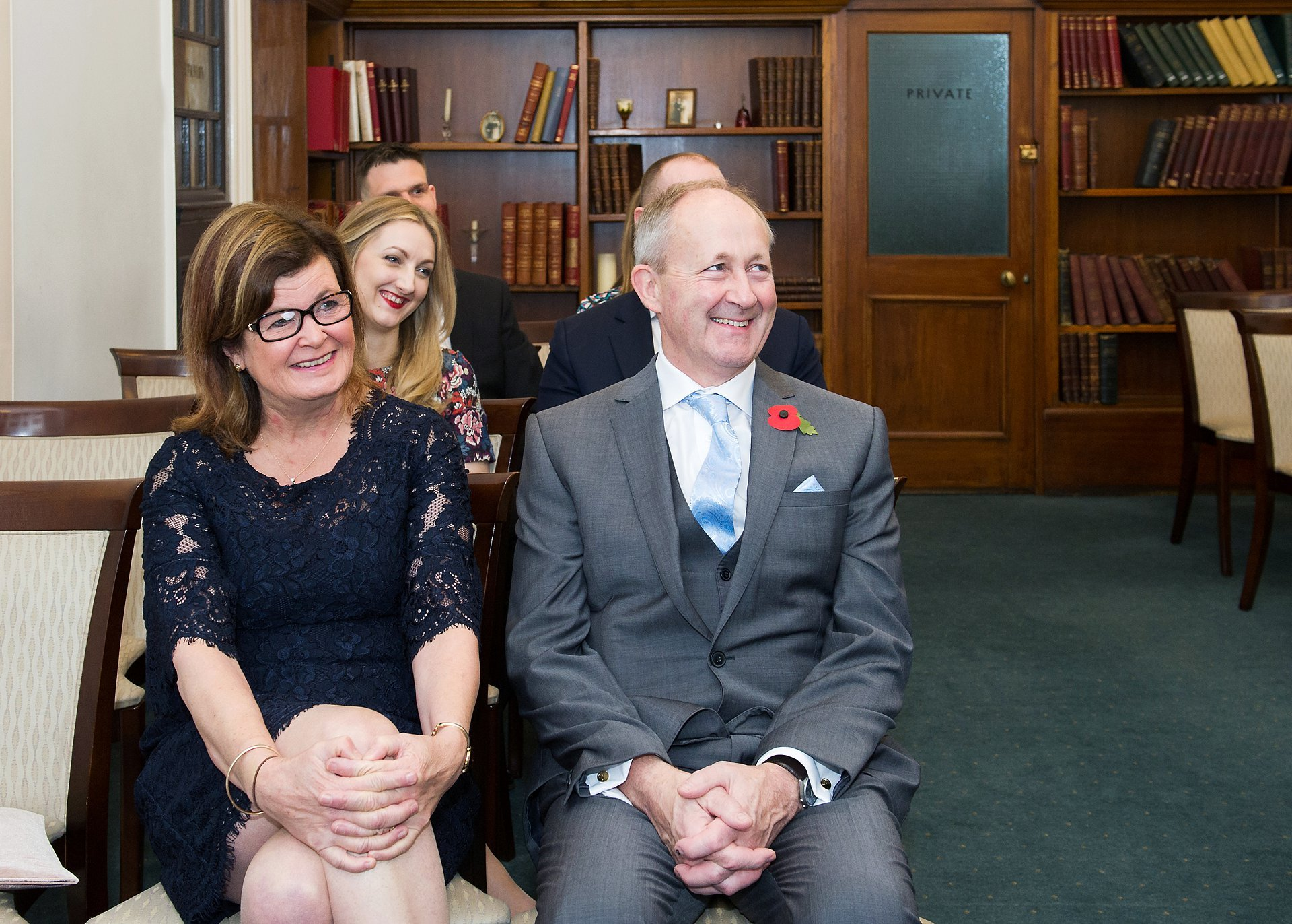 the groom's parents and family look on smiling during this mayfair library wedding