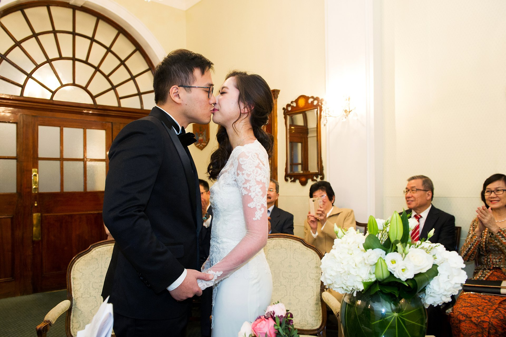 Bride and groom seal their marriage with a kiss in Chelsea's Rossetti Room with family and friends watching