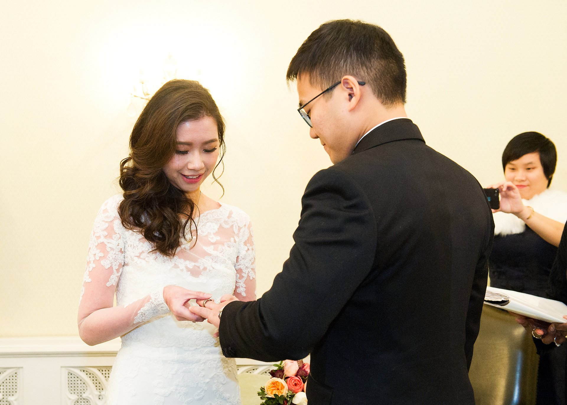 Bride places ring on groom's finger at Chelsea Old Town Hall wedding