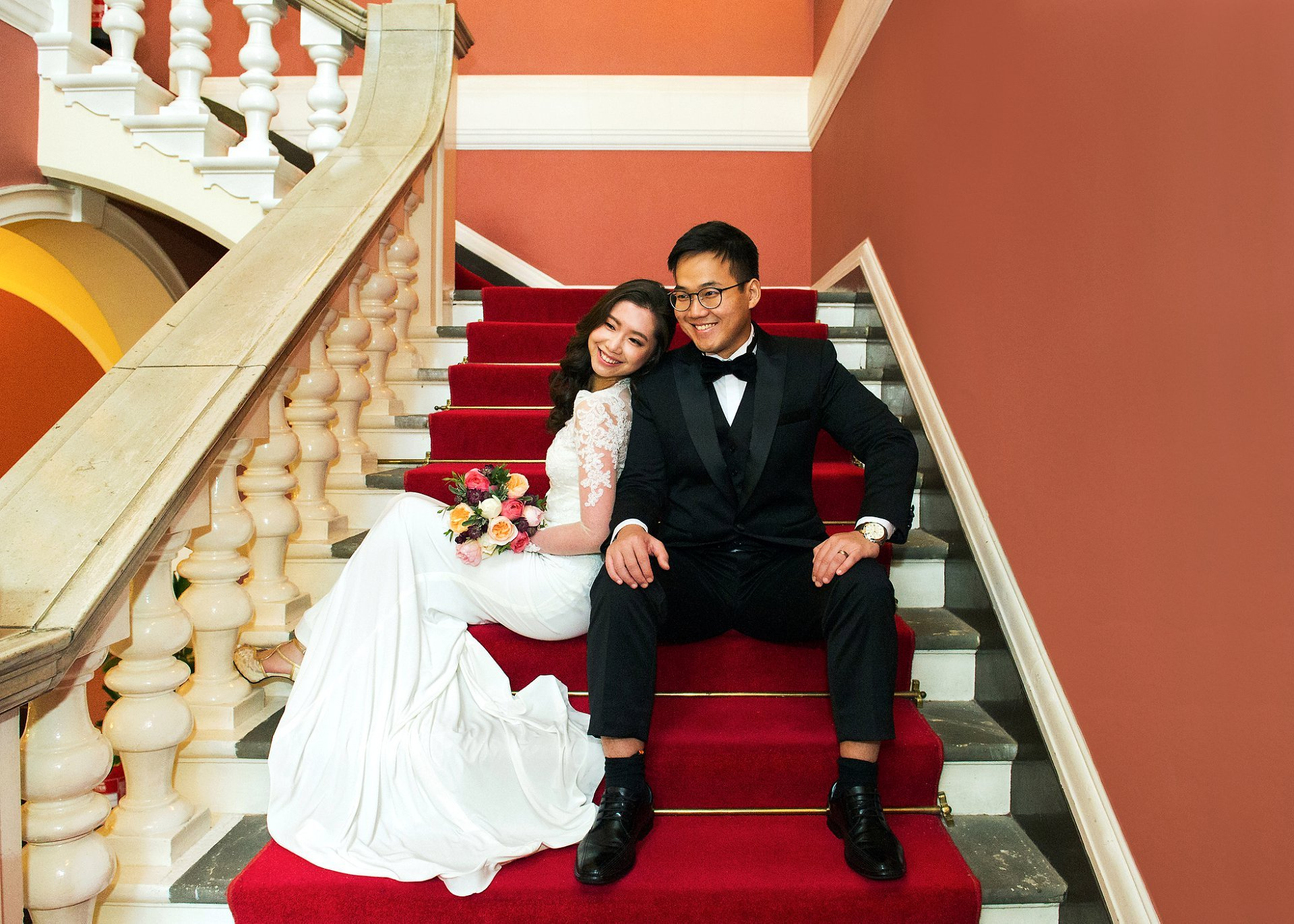 Chelsea Register Office wedding photographer bride and groom sat on red staircase