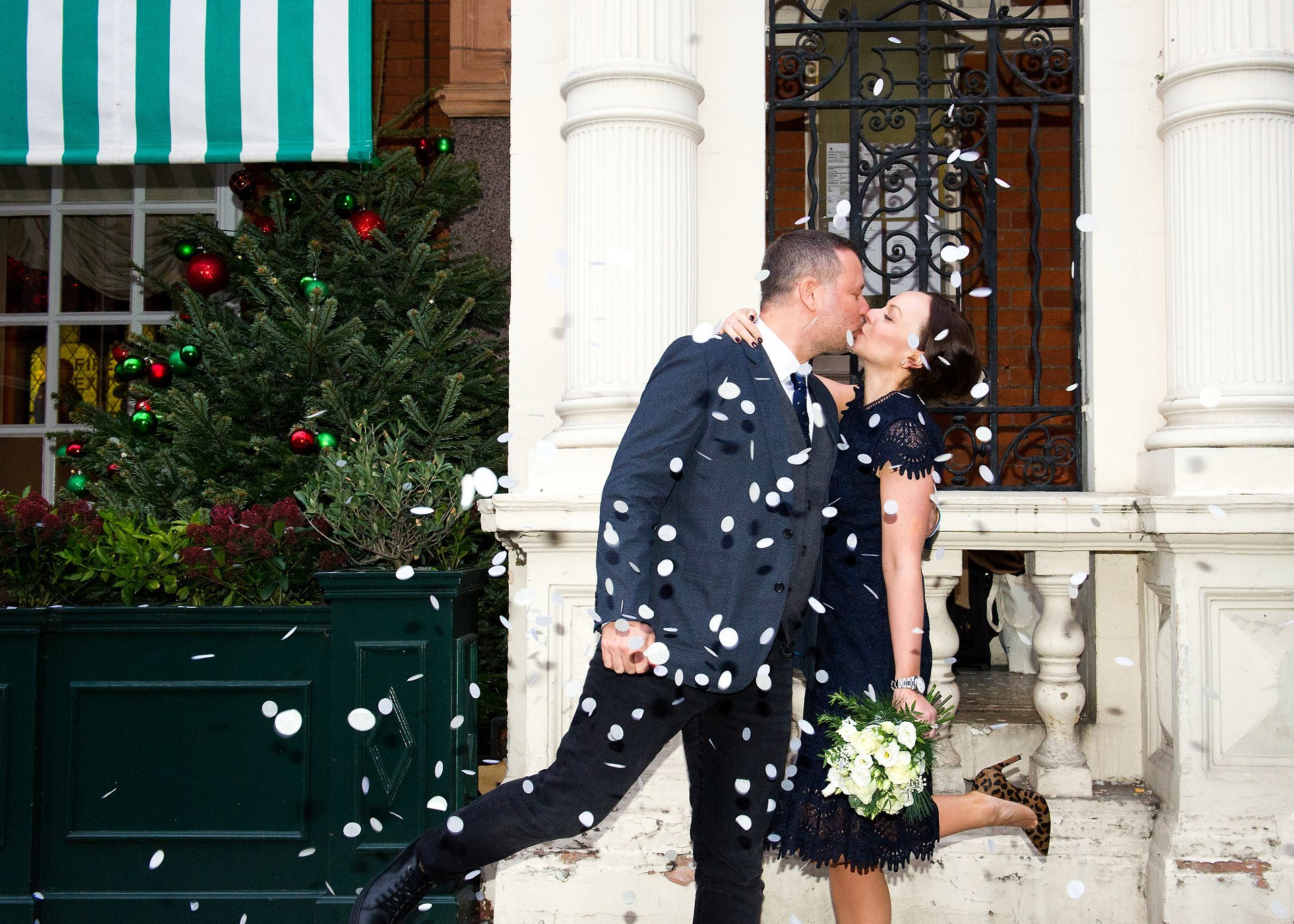 a bride and groom kissing under confetti london wedding photographer