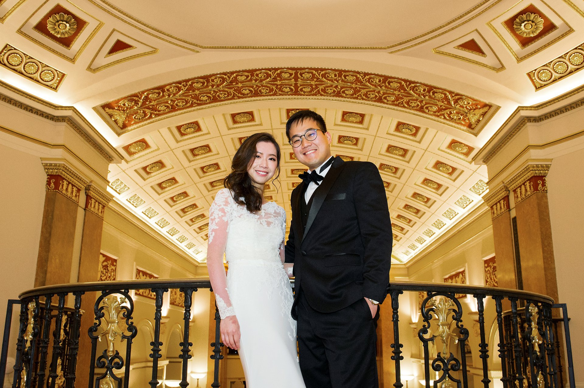 Lansdowne Club wedding photographer bride and groom in gallery with grand ceiling behind them