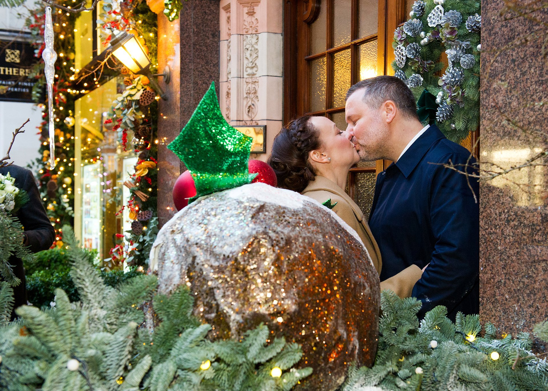 bride and groom kiss next to a christmas pudding after their old marylebone town hall christmas wedding