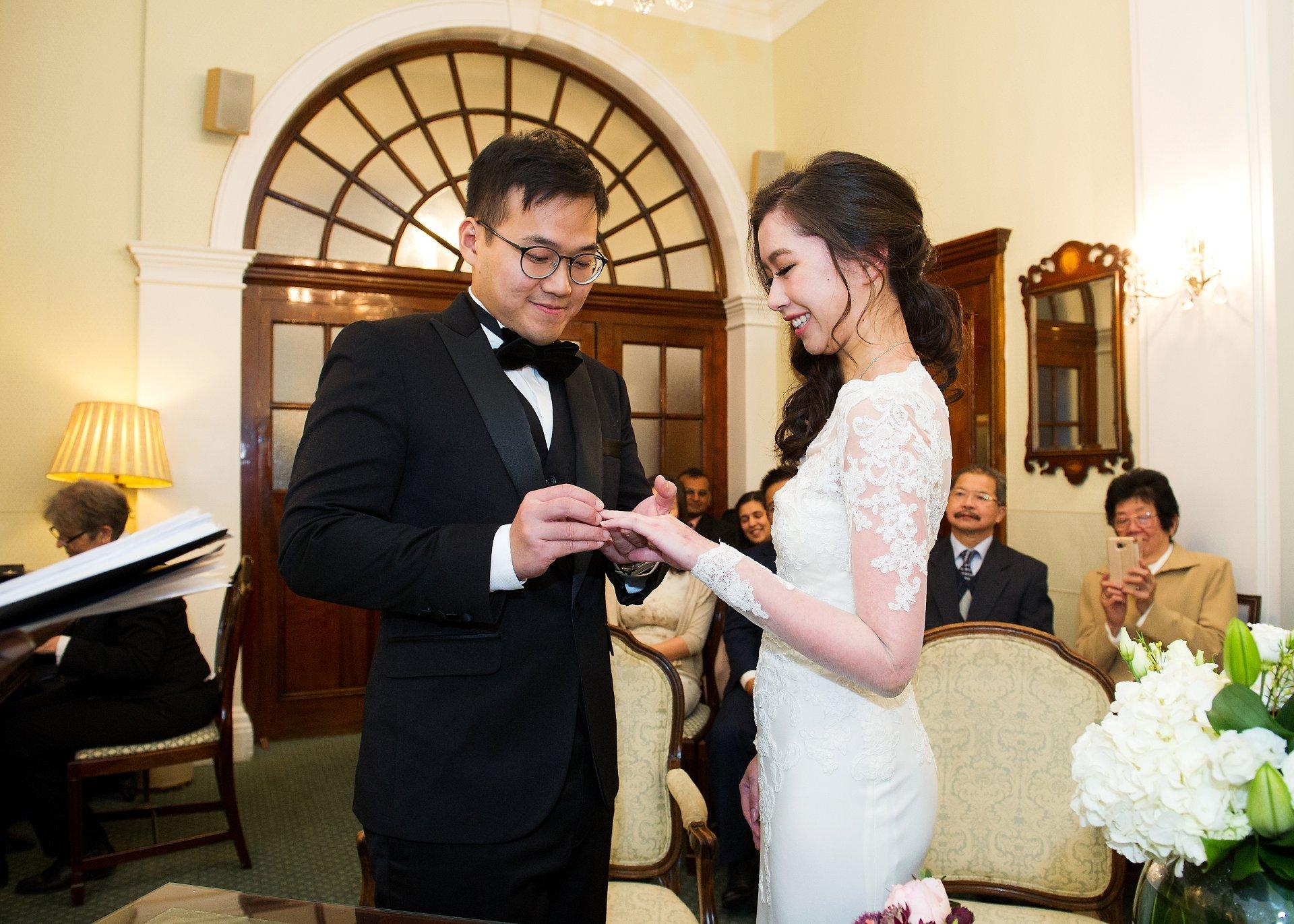 Rossetti Room Christmas wedding groom places ring on bride's finger