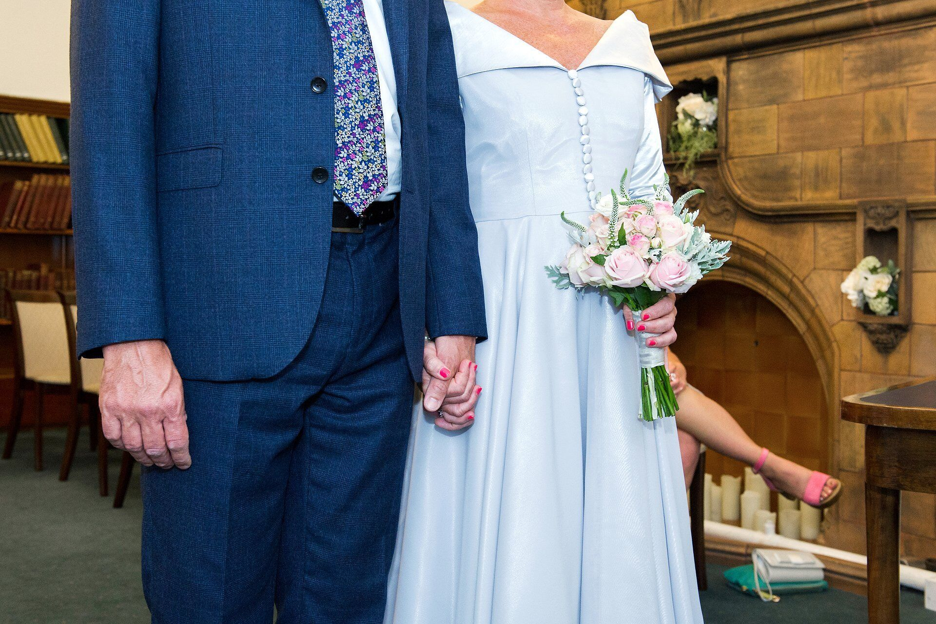 bride and groom hold hands during registry office wedding photographer